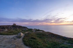 Wide-angle panorama of a beautiful lilac sunset overlooking the ocean with rocks in the foreground and a path leading up to a bunker.