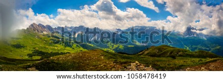 Wide angle panorama photo of Dolomites mountains, Italy. Summer hiking in Dolomites, north Italy. Picture of mountain peaks, nice valley and highlands in sunny weather with blue sky and low clouds.