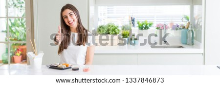 Wide angle picture of beautiful young woman eating asian sushi from delivery doing happy thumbs up gesture with hand. Approving expression looking at the camera showing success.