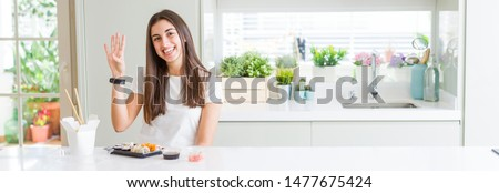 Wide angle picture of beautiful young woman eating asian sushi from delivery showing and pointing up with fingers number four while smiling confident and happy.