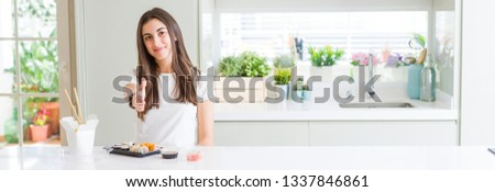 Wide angle picture of beautiful young woman eating asian sushi from delivery smiling friendly offering handshake as greeting and welcoming. Successful business.