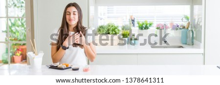 Wide angle picture of beautiful young woman eating asian sushi from delivery smiling with hands on chest with closed eyes and grateful gesture on face. Health concept.