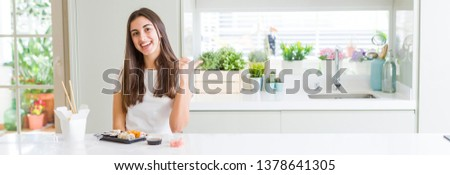 Wide angle picture of beautiful young woman eating asian sushi from delivery smiling with happy face looking and pointing to the side with thumb up.