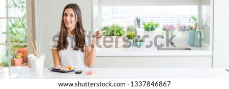 Wide angle picture of beautiful young woman eating asian sushi from delivery with a big smile on face, pointing with hand and finger to the side looking at the camera.