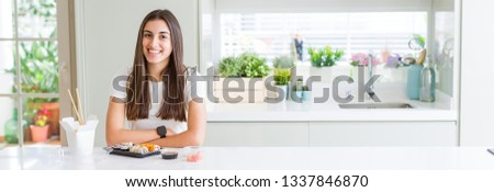 Wide angle picture of beautiful young woman eating asian sushi from delivery with a happy and cool smile on face. Lucky person.