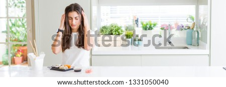 Wide angle picture of beautiful young woman eating asian sushi from delivery with hand on head for pain in head because stress. Suffering migraine.
