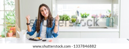 Wide angle picture of beautiful young woman eating delivery sushi celebrating surprised and amazed for success with arms raised and open eyes. Winner concept.