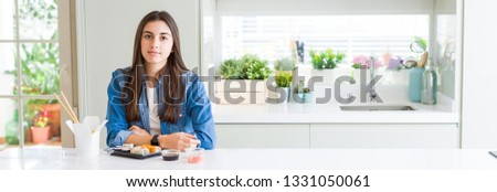 Wide angle picture of beautiful young woman eating delivery sushi with serious expression on face. Simple and natural looking at the camera.