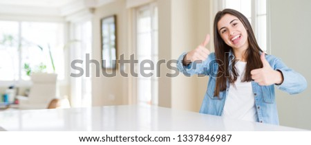 Wide angle picture of beautiful young woman sitting on white table at home approving doing positive gesture with hand, thumbs up smiling and happy for success. Looking at the camera, winner gesture.
