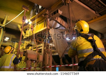 Wide angle picture of rope access riggers wearing safety harness, helmet commencing pulling a heavy duty chains block lifting load up at construction site Perth, Australia