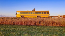 Wide angle, poetic shot of a man sitting on the top of a beautiful, bright yellow bus in the middle of the countryside. Sunny day.