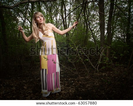 Wide-angle portrait of a young lady in a dark forest - stock photo