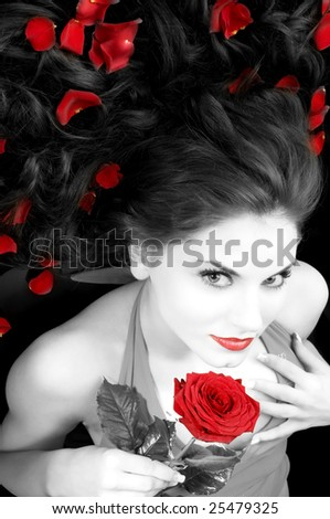 wide angle portrait of pretty woman with red dress rose and petals