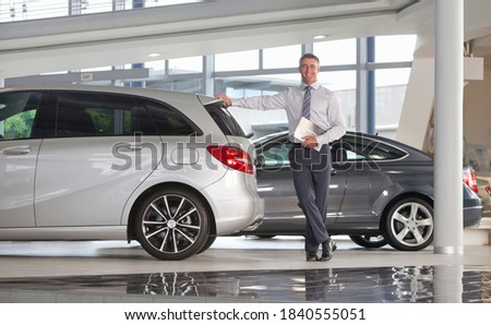 Wide angle Portrait of smiling salesman holding brochure and leaning on car in a car dealership showroom Foto stock ©