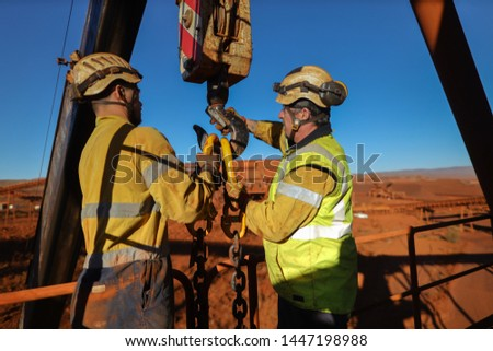 Wide angle shoot of male riggers wearing safety helmet holding and conducting crane lifting chain into crane lifting lug during shut down operation construction mine site