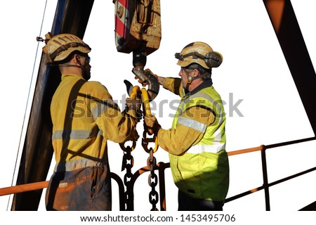 Wide angle shoot of male riggers wearing safety helmet personnel protection (PPE) equipment  holding clipping crane lifting hook into chain crane lifting lug lifting load isolated white background