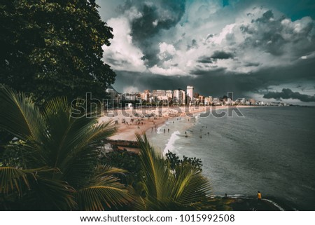 Wide-angle shooting of stunning cityscape during the storm in Rio de Janeiro: coastline with Leblon and Ipanema beaches, swimming and tanning people, dramatic sky with heavy rain in distance, palms
