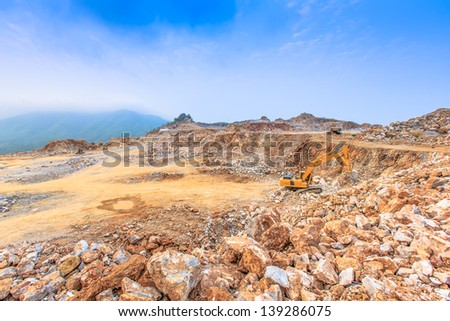 wide angle shot excavator loading crushed rock on dumper truck at dolomite mines site with blue sky background - stock photo