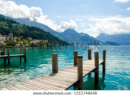 Wide angle shot: landing stage, ship station in central Switzerland, taken during a boot trip on the  idyllic Lake Lucerne with mountains, sky and clouds in the background