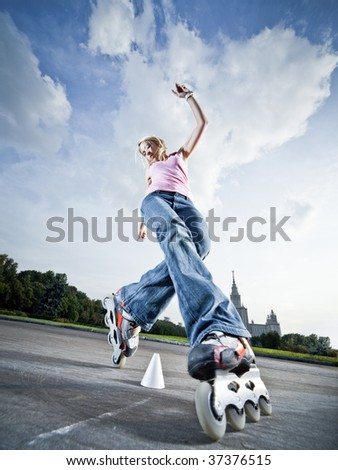 Wide-angle shot of a rollerblading girl performing 'compass' element - little motion blur