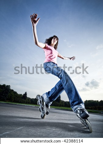 Wide-angle shot of a rollerblading girl performing \'compass\' element - little motion blur