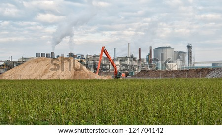 wide angle shot of a sugar mill factory with a sand hill in front