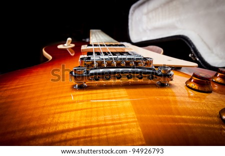 Wide Angle Shot of a Sunburst Electric Guitar Laying in a Hard Shell Electric Guitar Case