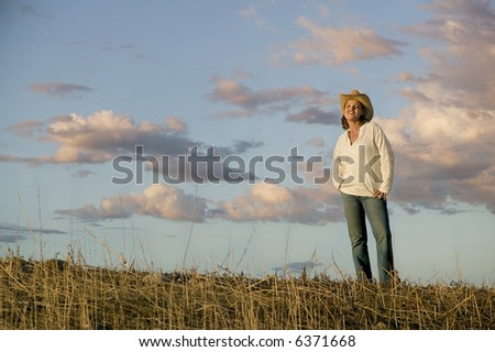 Wide angle shot of a western woman against a cloudy sky at dusk.