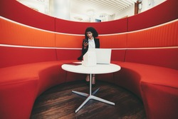 Wide-angle shot of a young charming African-American businesswoman sitting on a curved sofa of red color in an office lounge and using her phone; laptop, digital tablet, charging station on the table