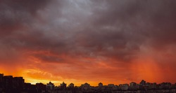 Wide angle shot of dramatic stormy sunset sky with clouds over city skyline background.