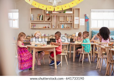 Wide Angle Shot Of Pupils Working At Tables In Montessori School #641733190