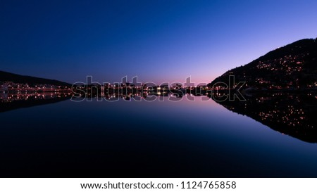 Wide-angle shot of the late sunset above Bergen city center mirrored in the large lundegaards-lake. The symmetrical result is reminicent of the mandelbrot fractal