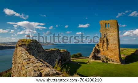 Photo of  Wide angle shot of the medieval Scarborough Castle during sunset golden hour against a bright blue sky, Yorkshire, England, UK