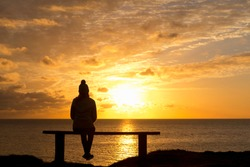 Wide angle shot of the Silhouette of a woman sitting on a bench looking at the tranquil sunset over the ocean