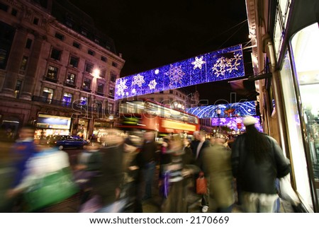 Wide angle shot of very busy Oxford Street, central London with crowd visiting the shops for festive shopping showing  movement blur.