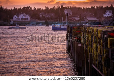 Wide angle shot of working fishing community in Maine at sunset.  Water and lobster traps in the foreground.