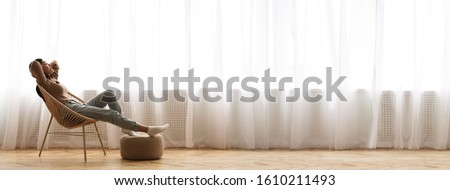 Wide Angle Shot Of Young Asian Girl Relaxing In Modern Wicker Chair Near Window, Enjoying Home Comfort, Extreme Long Banner, Panorama With Free Space