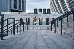Wide angle shot of young athletic woman jumping upstairs, running training at urban city stadium