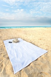 Wide angle towel on the beach, with hat and sunglasses.