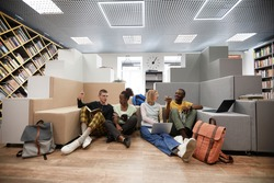 Wide angle view at diverse group of young students studying together while sitting on floor in college library, copy space