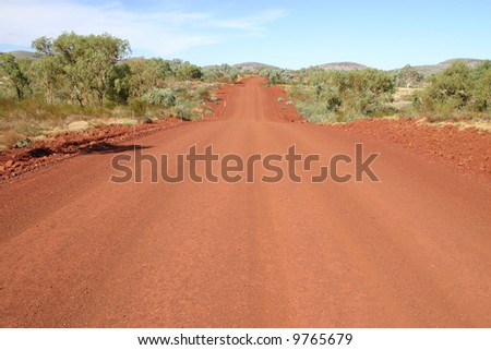 Wide angle view at red gravel country road in Australia.