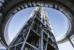 Wide-angle view from the bottom of a modern oil refinery or a contemporary fuel factory facility in an industrial zone, surrounded by a round bridge, with plenty of pipes, metal beams, and stairs