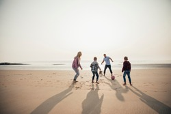 Wide angle view of a family playing football at the beach.