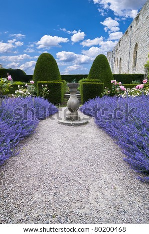 wide angle view of a gravel pathway leading through lavender beds to an old stone sundial and formal trimmed hedges behind