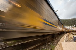 Wide angle view of a moving train at the Kalkbay Rail Road crossing in Cape Town in the Western Cape of South Africa