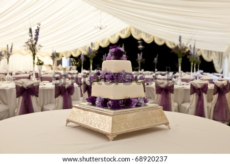 Wide angle view of a wedding cake with venue in background, slightly out of focus