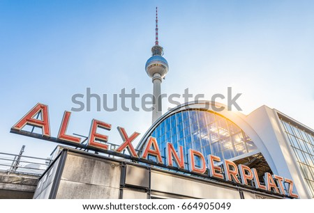 Wide-angle view of Alexanderplatz neon sign with famous TV tower and train station in golden evening light at sunset in summer, central Berlin Mitte district, Germany