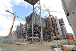 Wide angle view of an industrial construction site with cranes and steel structure