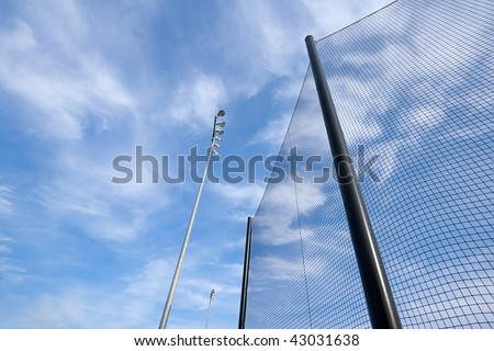 Wide angle view of backstop net and stadium lights at baseball or softball playing field. Angle is looking up towards the sky. Good abstract shot or background.