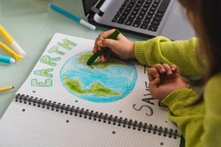 Wide angle view of child girl draws planet earth with wax colors on school notebook for Earth day - Little activist girl writes the message Save the Planet - Protection of environment, global warming